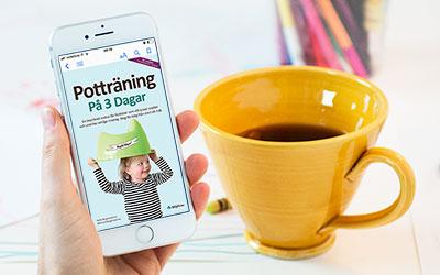 Boken Potträning på 3 dagar på mobilen med kaffekopp i bakgrunden