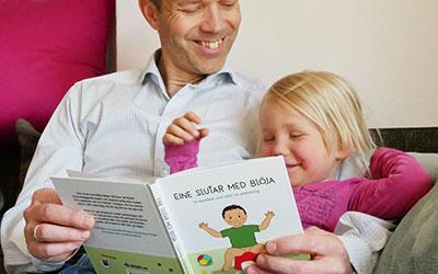 Pappa med barn läser boken Eine slutar med blöja