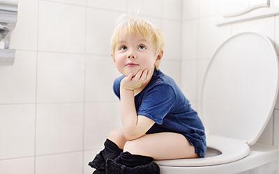 Barn som sitter på toalett och toalettränar